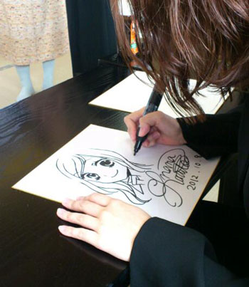 サインペン一発描きに震えながら色紙を描く春田。